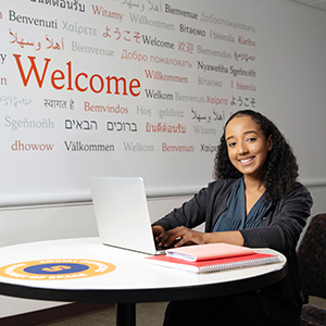 Student behind welcome sign